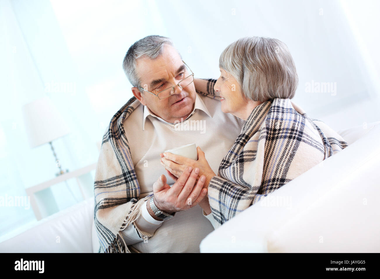 Portrait of a happy senior couple wrapped in plaid sitting at home - Stock Image
