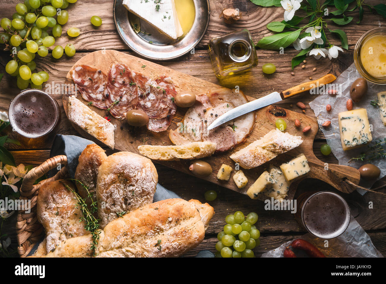 Homemade bread, cheese, olives, grapes and flowers on old boards horizontal - Stock Image