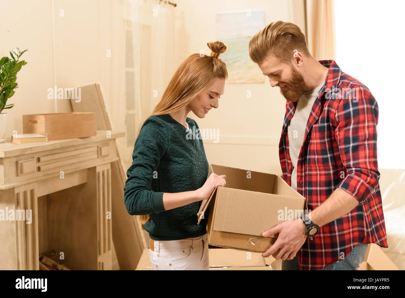 side view of young smiling couple looking into cardboard box at new home - Stock Image