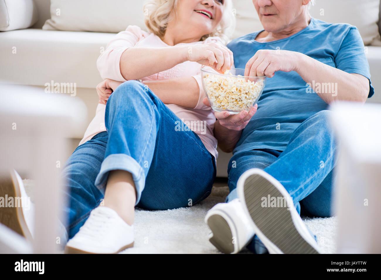 Cropped shot of happy senior couple eating popcorn on sofa - Stock Image