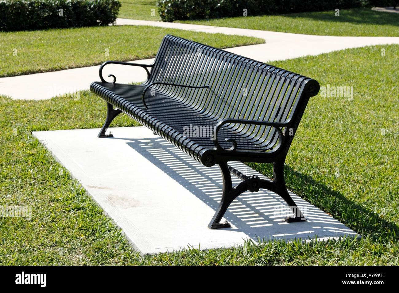 Black Metal Two Seat Park Bench On A Concrete Slab