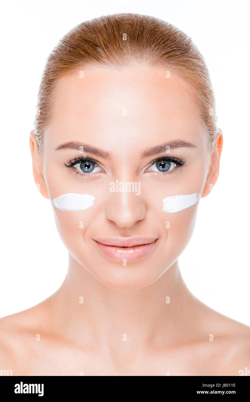 portrait of smiling woman with face cream looking to camera on white - Stock Image