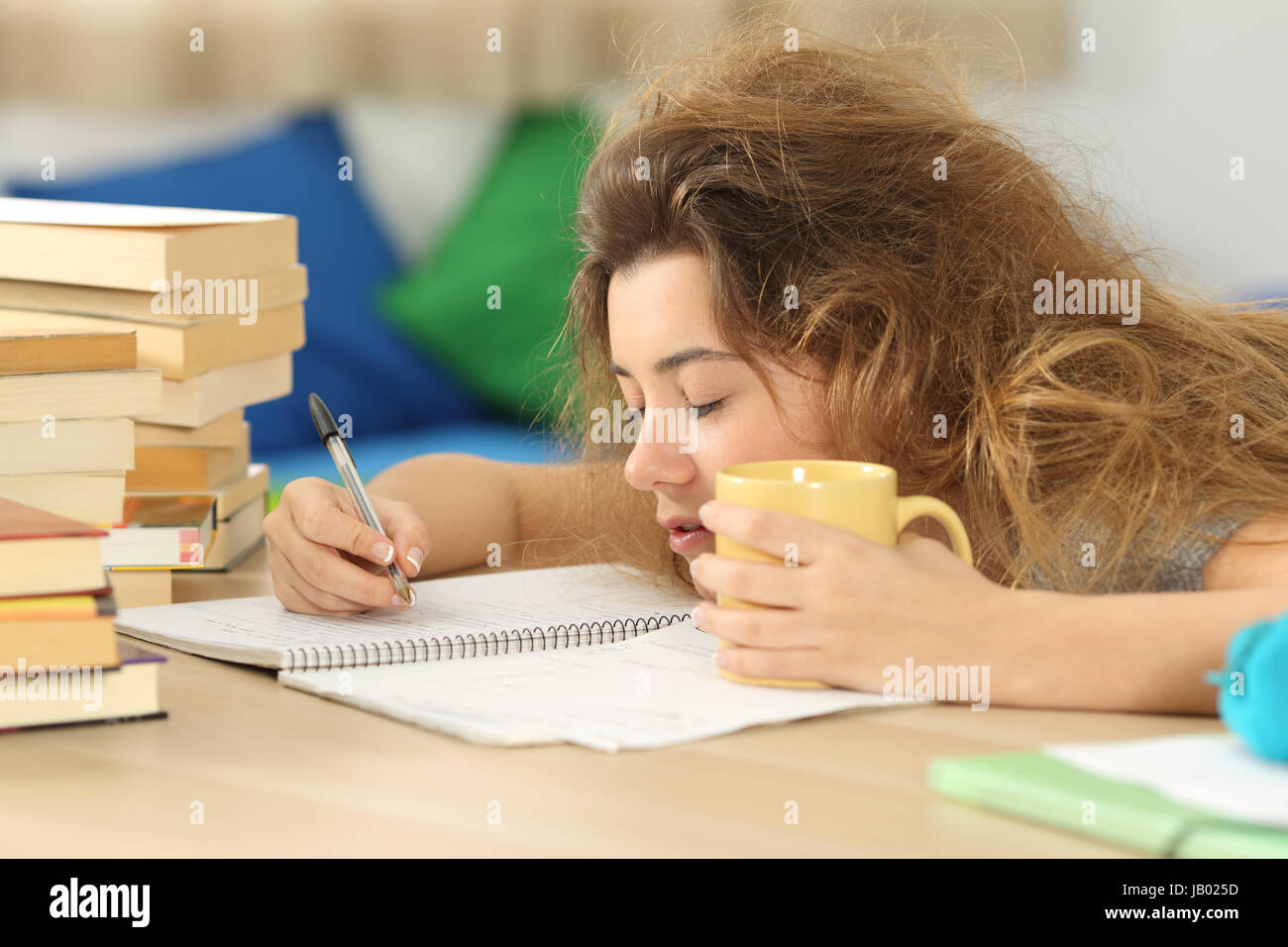 Tired and sleepy student with tousled hair trying to write notes on a desk in her room in a house indoor - Stock Image