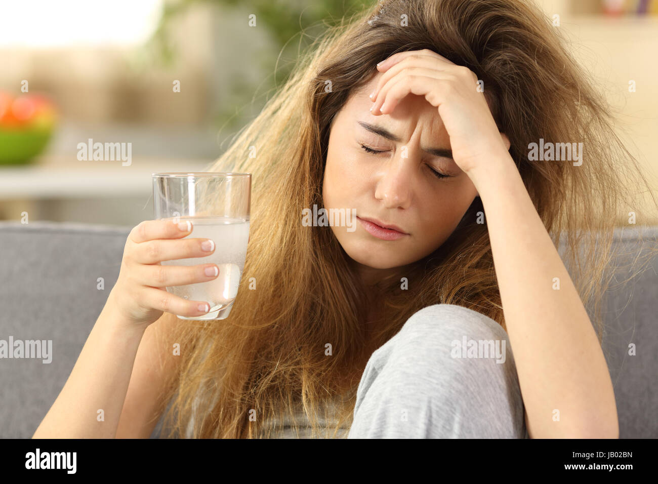 Front view of a teen with tousled hair suffering head ache sitting on a couch in the living room at home Stock Photo