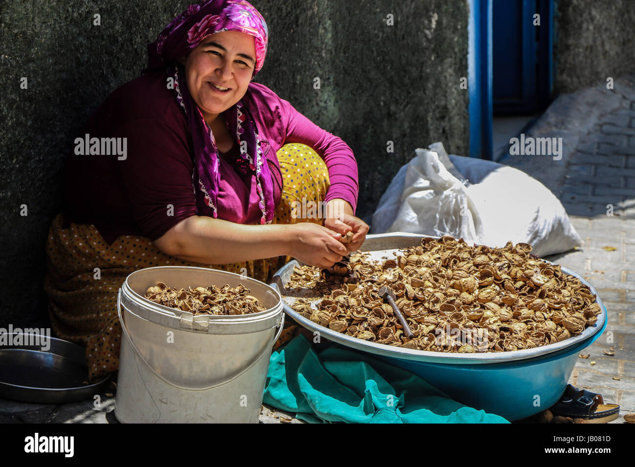 June 3, 2017 - A woman cracks walnuts to remove the shell in