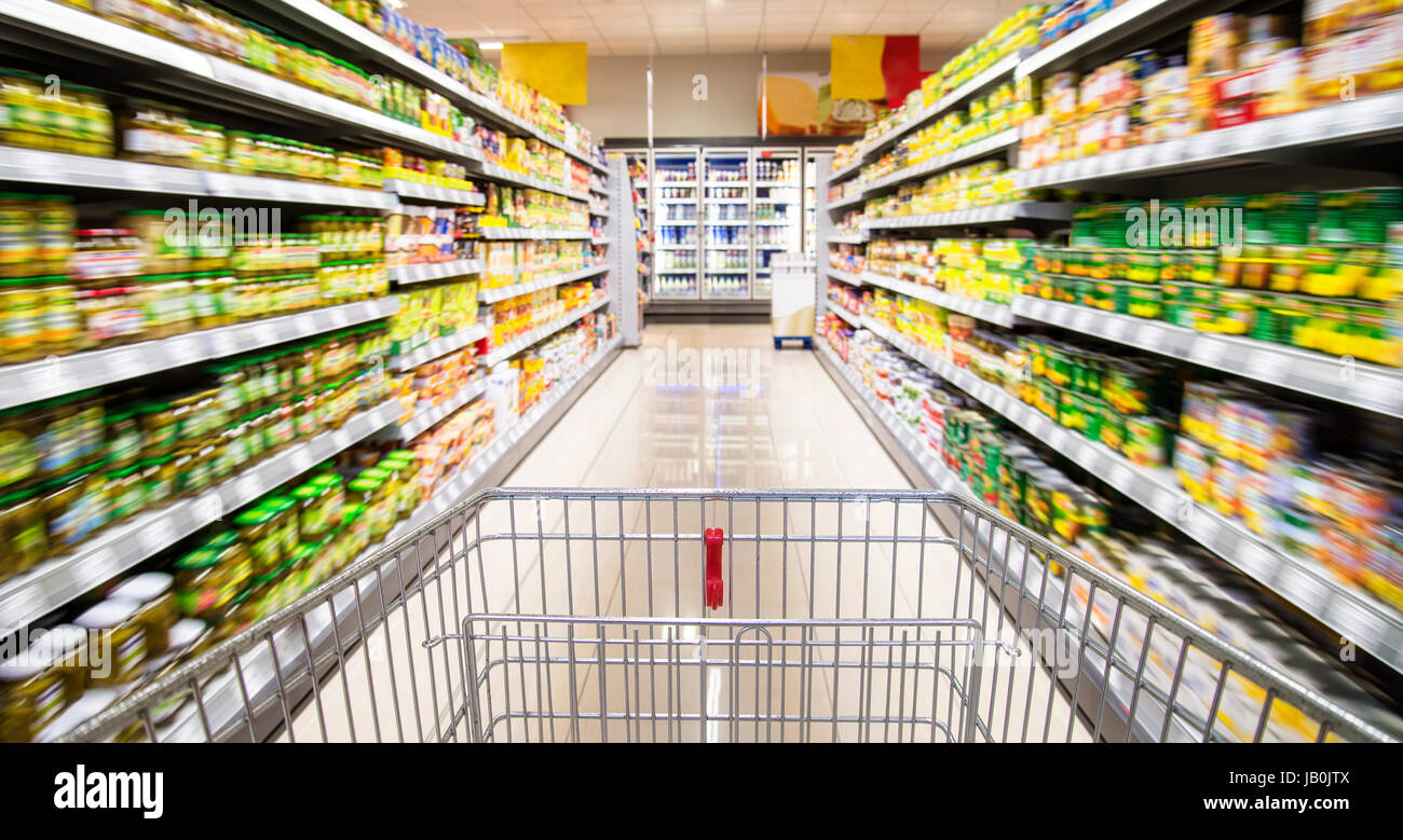 An empty shopping cart between rows of shelves in the supermarket. - Stock Image