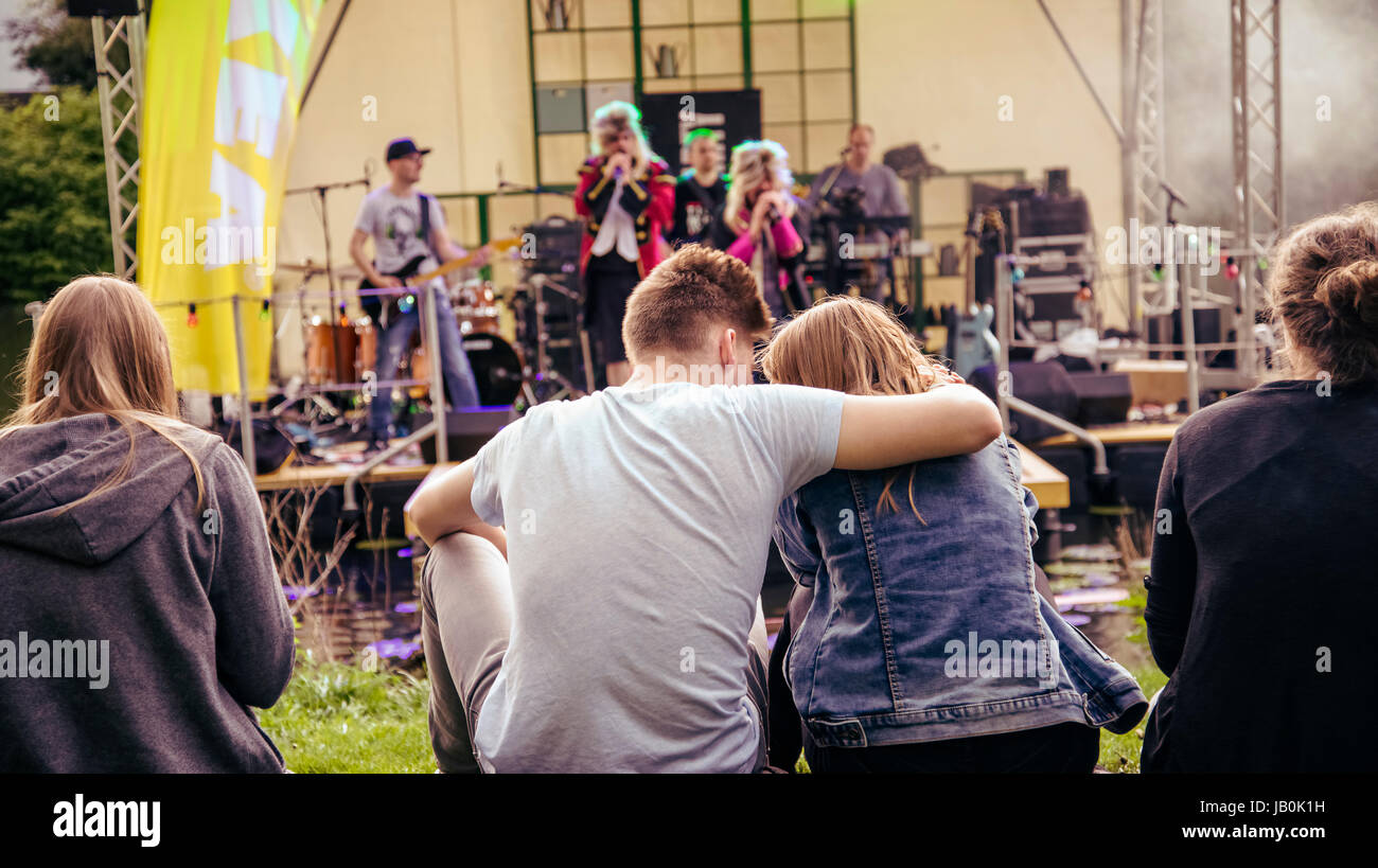 Young couple in front of stage at an open air concert. During a public event of Ikea on the banks of the river Lahn - Stock Image