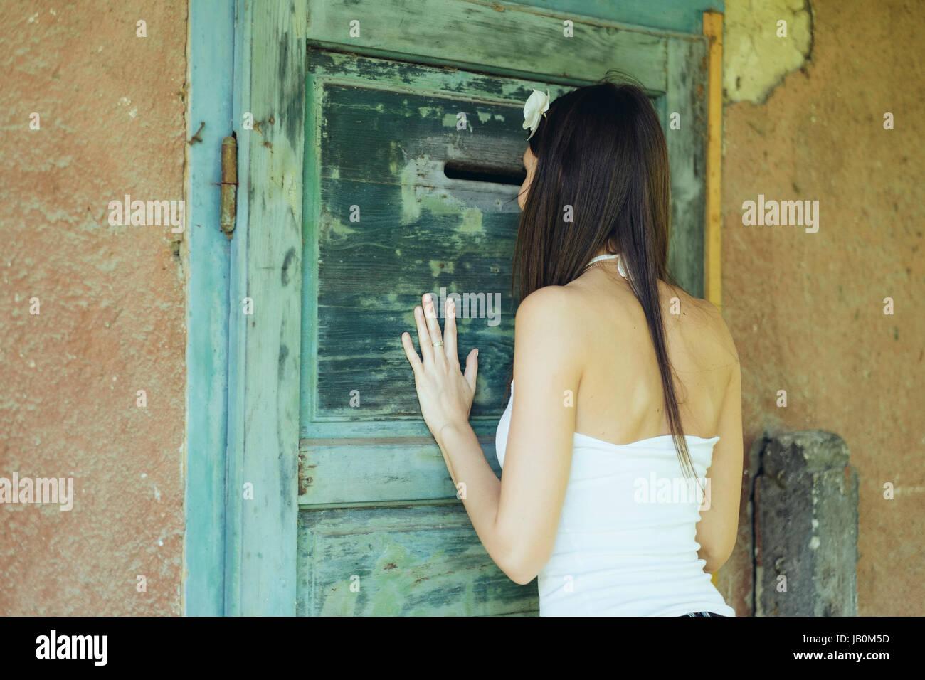 Woman watch keyhole - Stock Image