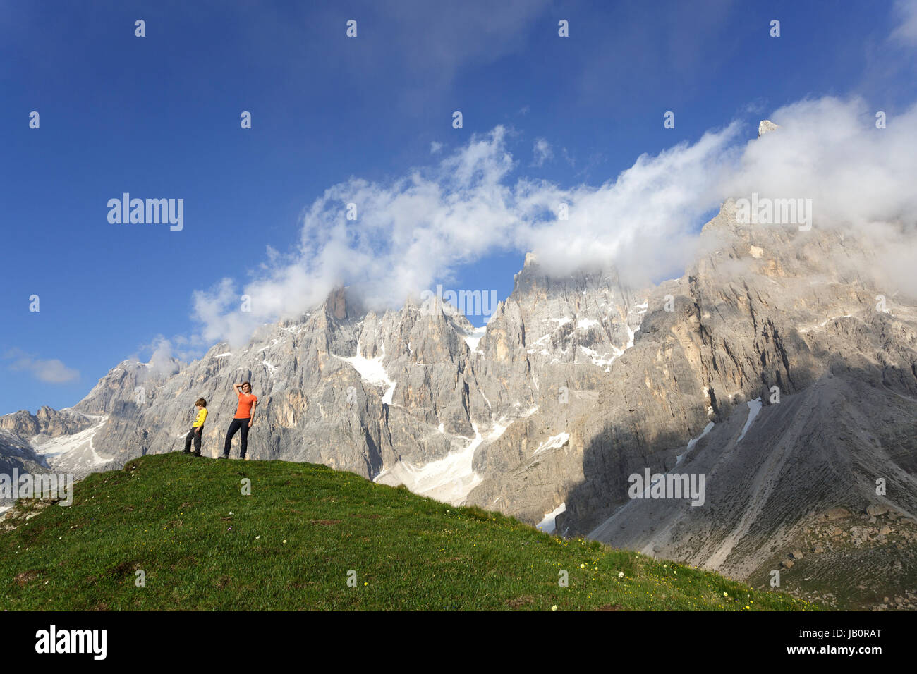 Mother and son standing on a hill under the mountains near pasoo Rolle, Dolomiti, Italy. - Stock Image