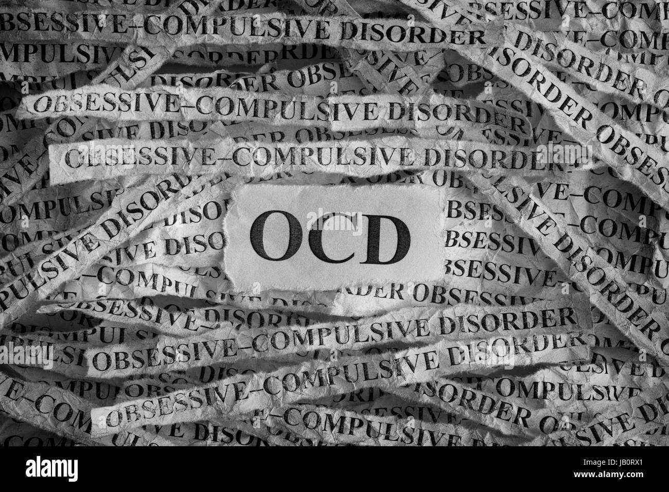 Obsessive compulsive disorder (OCD). Torn pieces of paper with the words Obsessive compulsive disorder. Concept - Stock Image