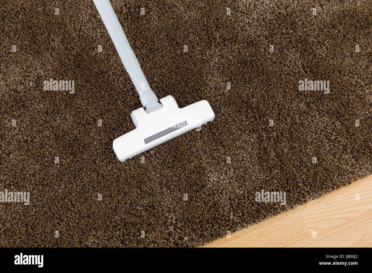 Brown carpet with vacuum cleaner - Stock Image