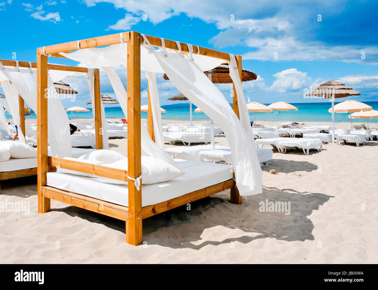 view of some beds in a beach club in a white sand beach in Ibiza, Spain - Stock Image