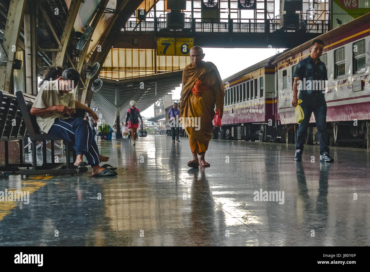 Hua Lamphong train station in Bangkok, Thailand. A monk and other travellers on platform with stationery train. - Stock Image