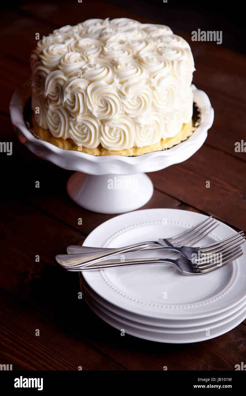 carrot cake, white frosting, swirls, plates. forks, white platter, dark wood background, white, bright - Stock Image