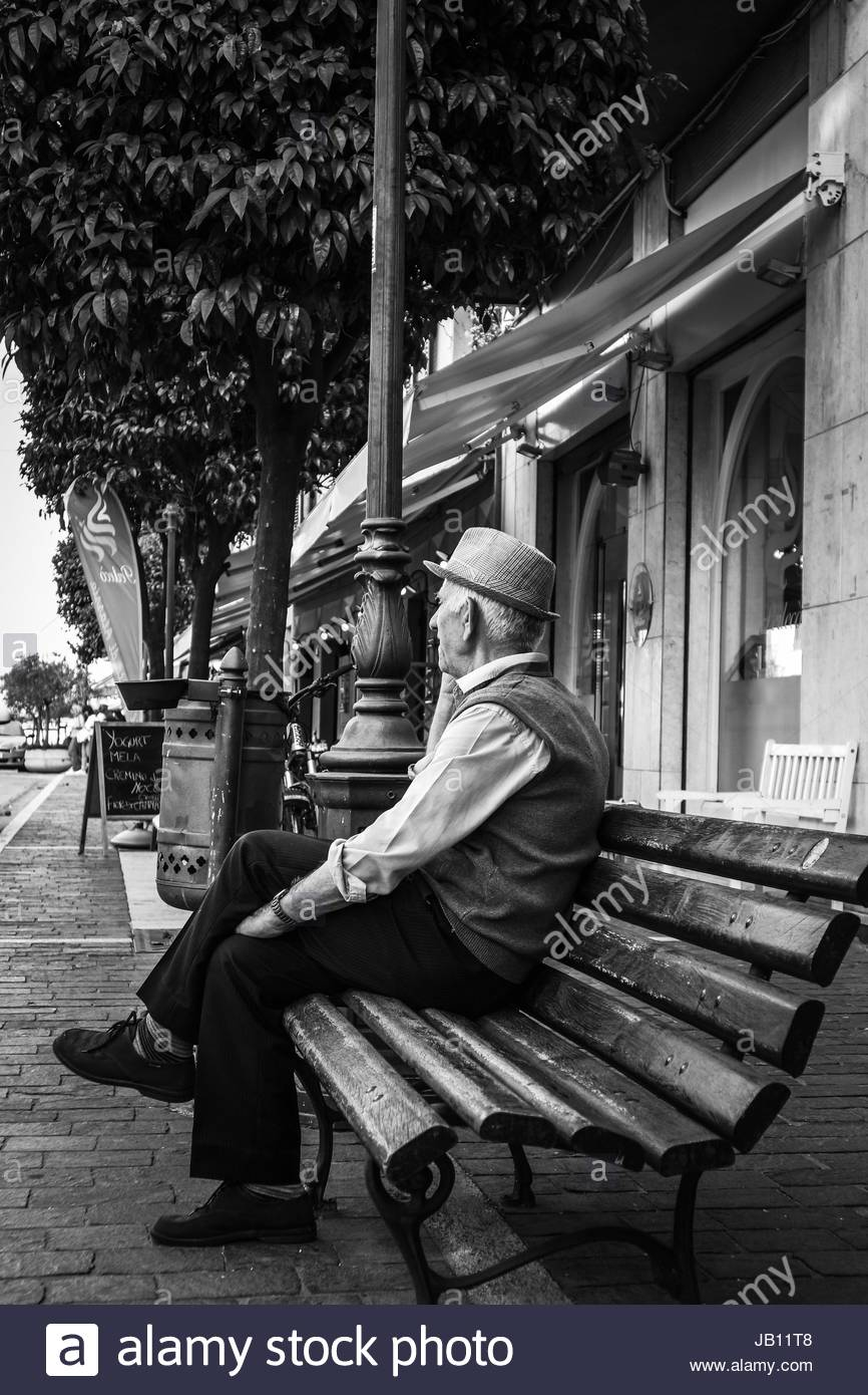 Old man sitting on a bench - Stock Image
