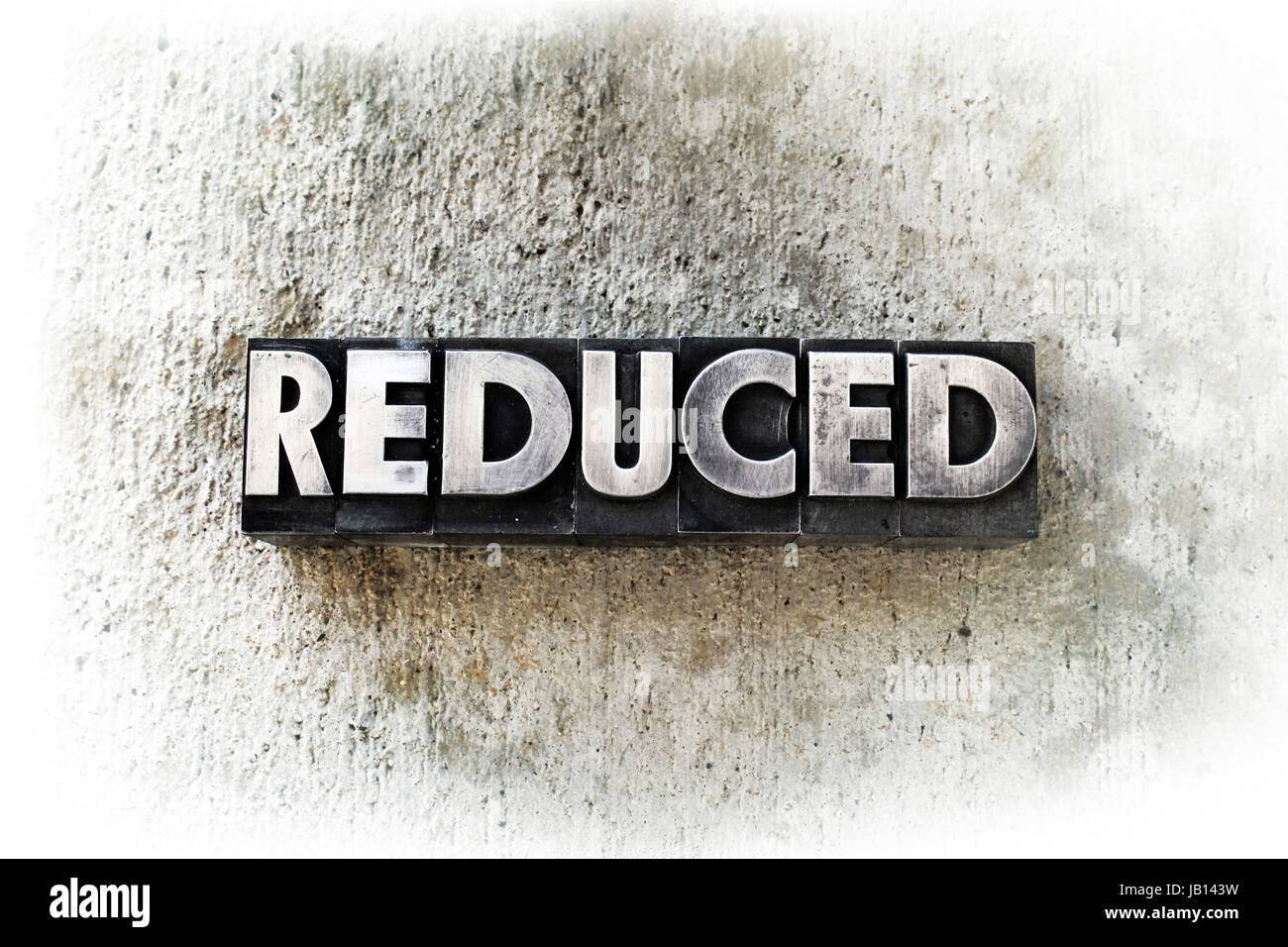 The word 'REDUCED' written in old vintage letterpress type. - Stock Image