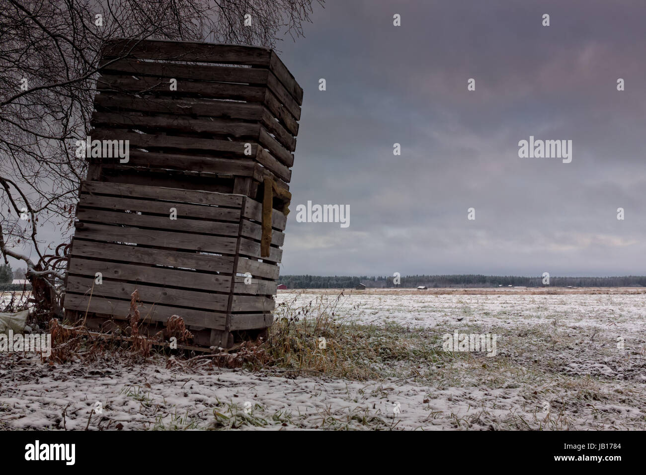 Two wooden crates stacked on a frosty field in the Northern Finland. These boxes are typically used for storing Stock Photo