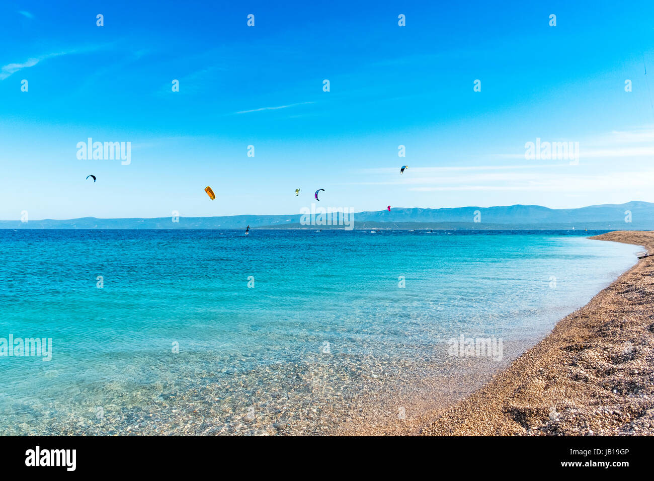 Low level shot of the landmark Golden Horn at the island Brac in Croatia. Kitesurfer in the background enliven the - Stock Image