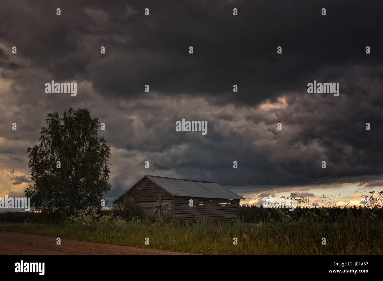 The warm summer day is turning into a thunder storm in the Northern Finland. The weather in these parts can be quite - Stock Image