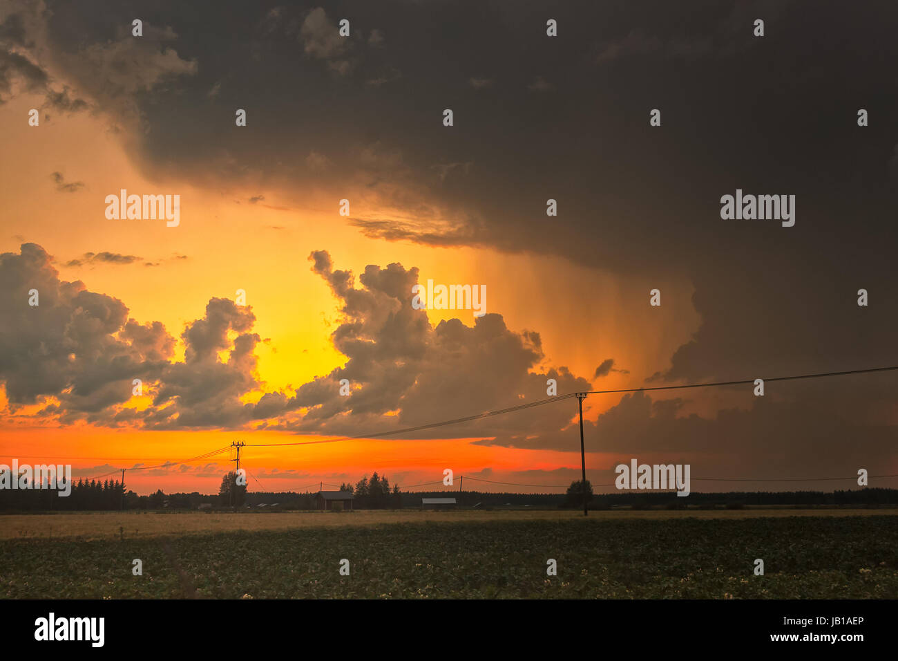 The heavy summer rain gives space for a beautiful sunset in the  Northern Finland. The  summer weather can be quite - Stock Image