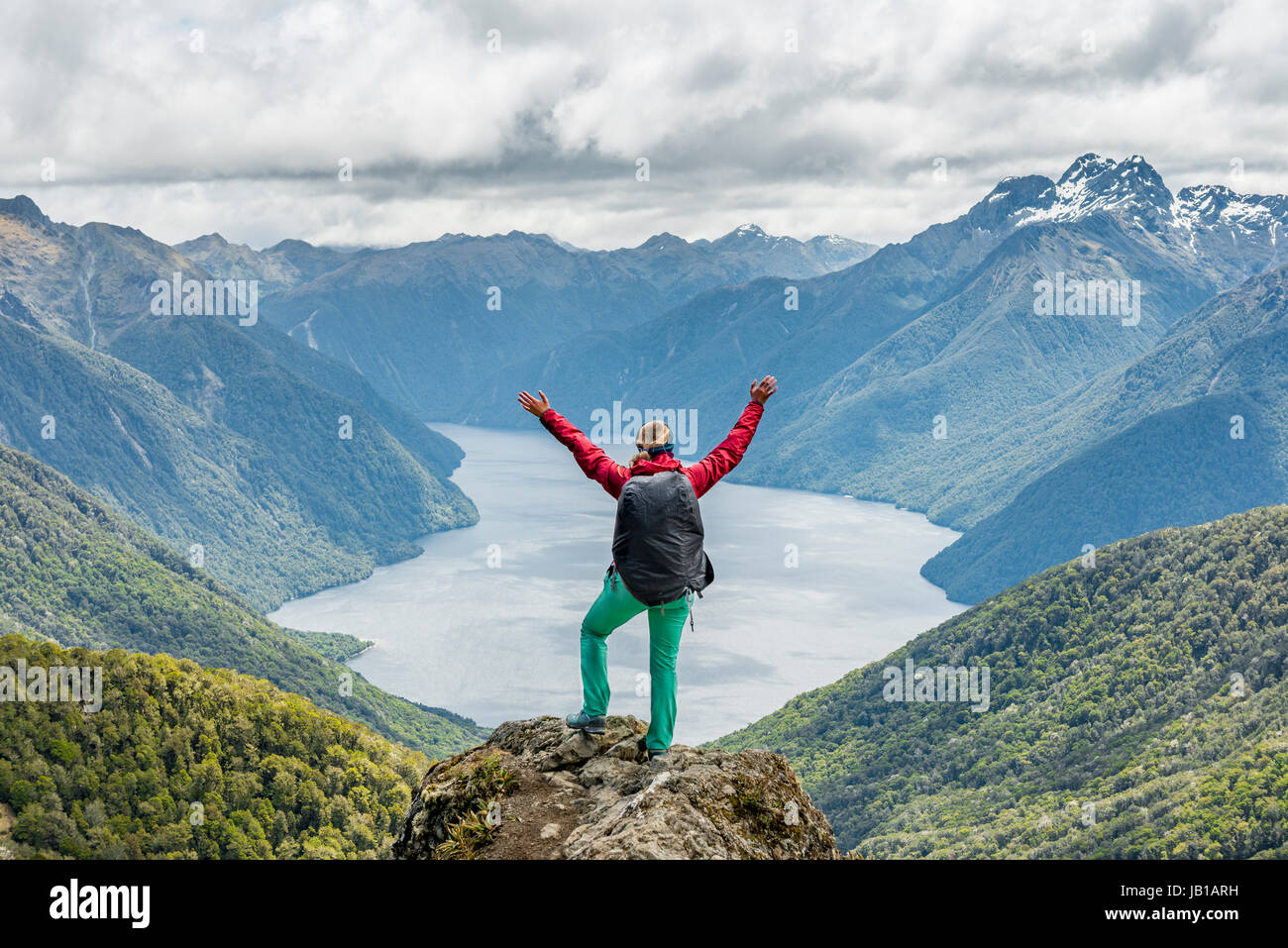 Female hiker is looking at the South Fiord of Lake Te Anau, stretching arms in the air, at back the Southern Alps Stock Photo