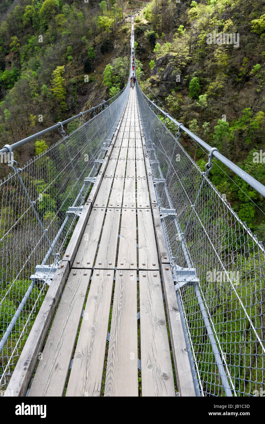 Sementina, Switzerland: people walking on the suspension bridge over the valley at Semerntina on the Swiss alps - Stock Image