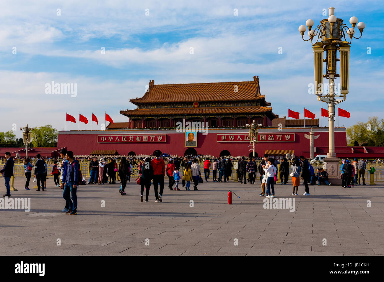 Tourists stroll around Tiananmen Square where a portrait of Mao is prominently displayed - Stock Image
