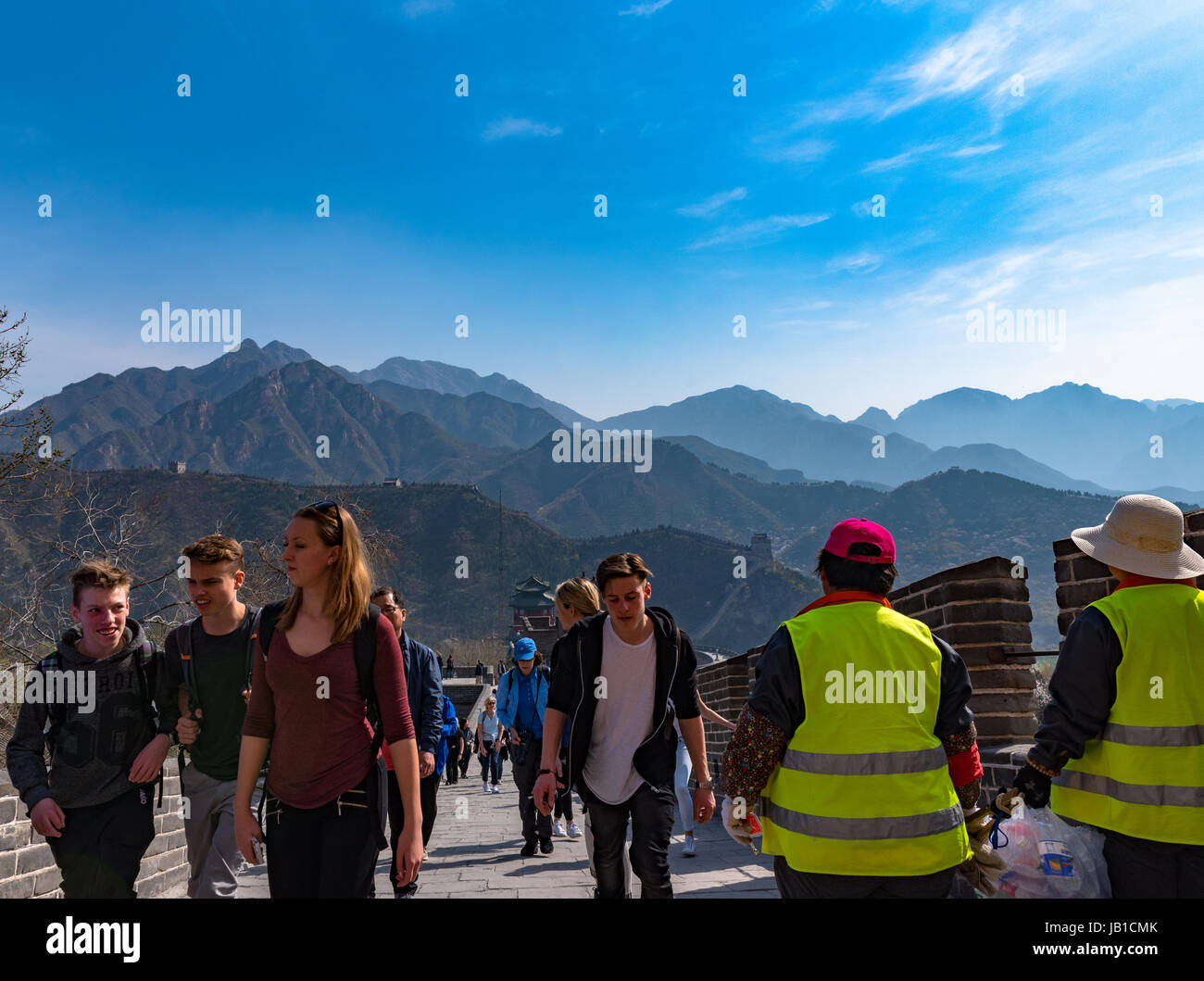 Tourists make thier way up along the Great Wall of China with mountains in the background - Stock Image