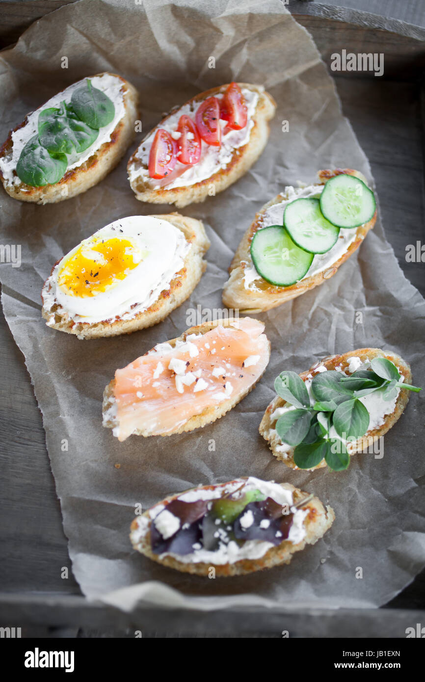 Homemade crostinis with various toppings - Stock Image