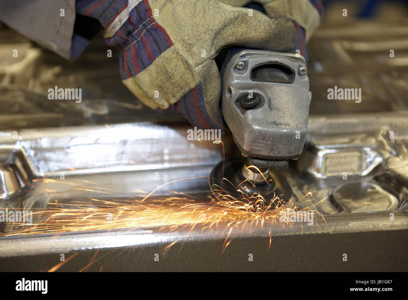 man using a angle grinder on metal surface with sparks Stock Photo