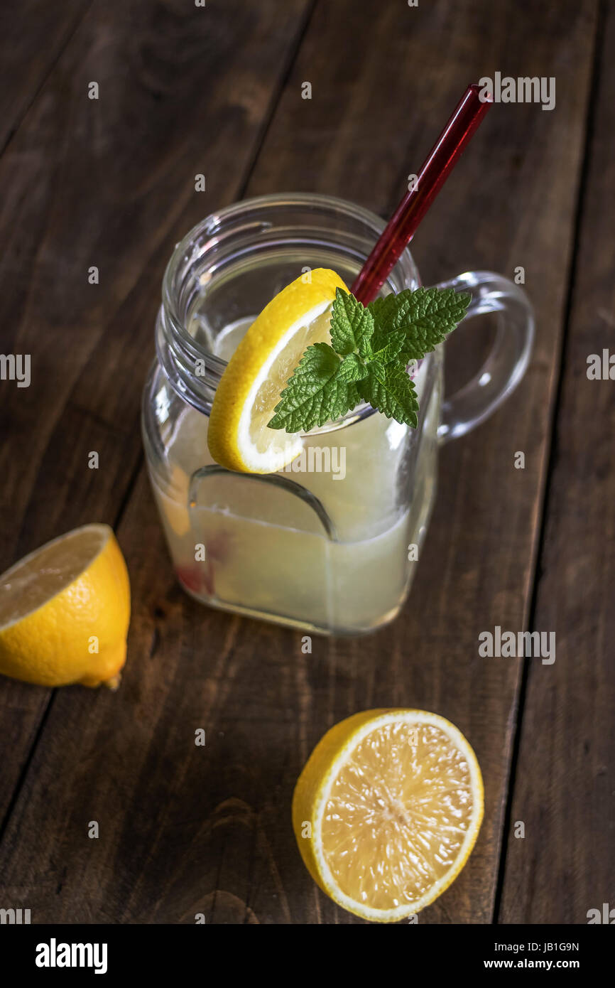 Lemonade glass jar with lemon wedges and straw, from above - Stock Image