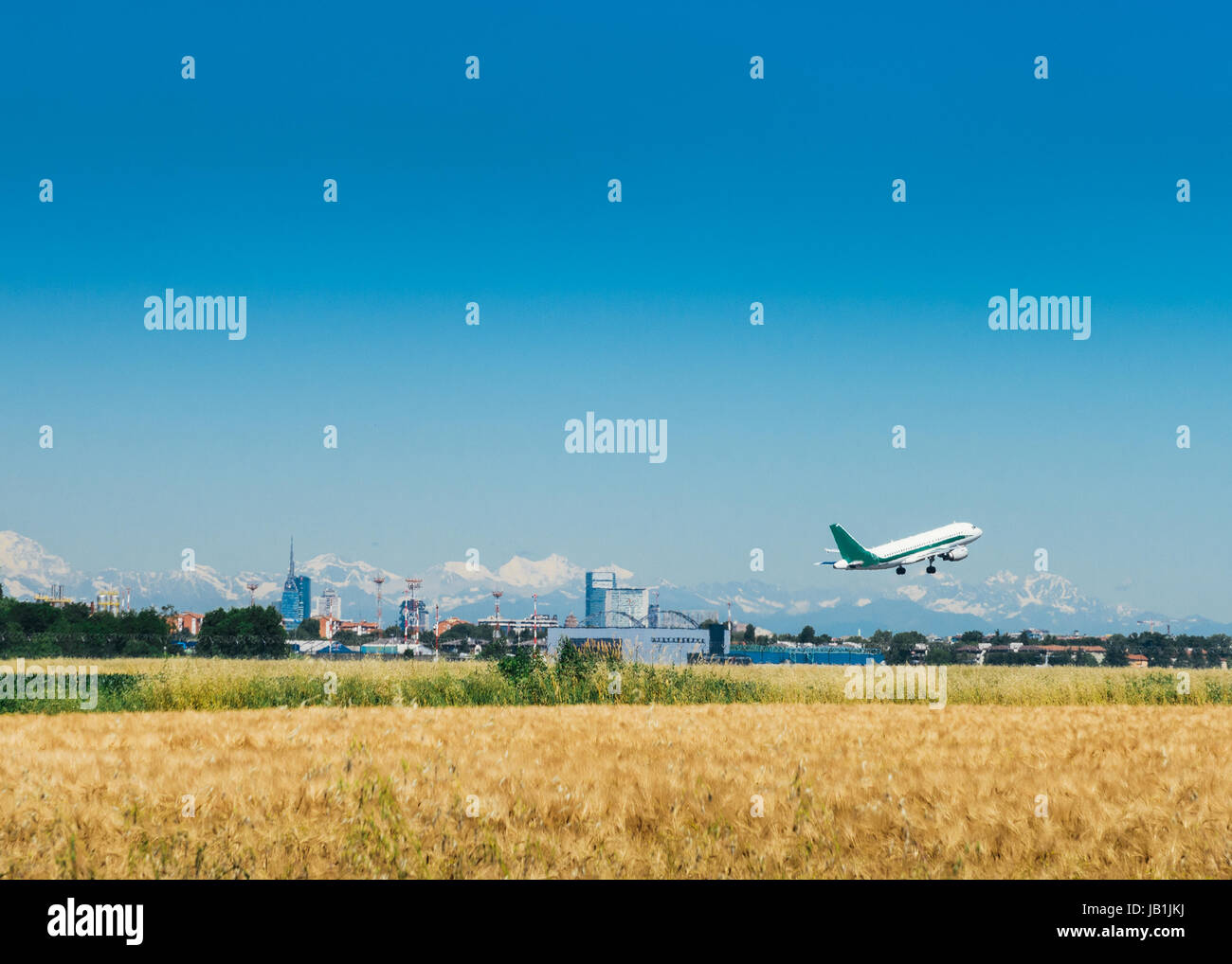 A commercial airplane takes off from Milan with the city skyline in the background and Italian alps also visible - Stock Image