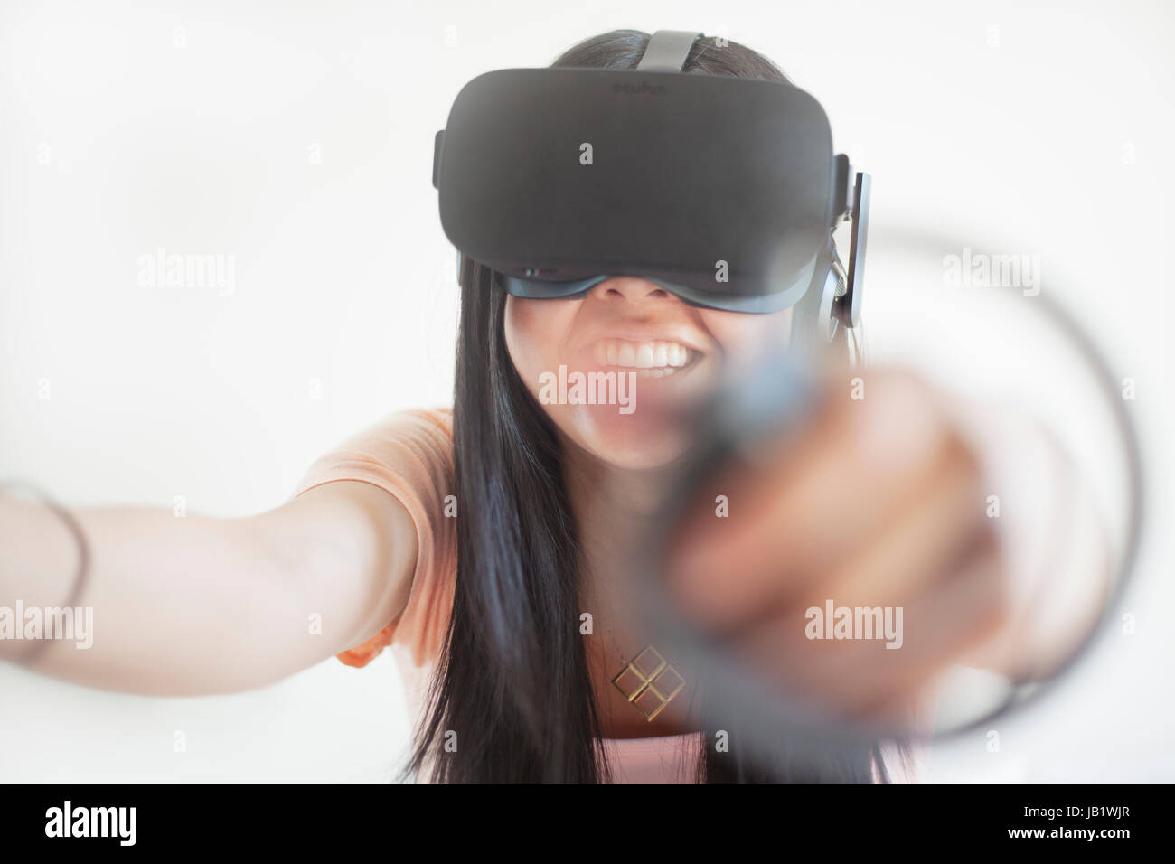 Young Asian woman wearing virtual reality headset Oculus Rift and demonstrating how to use the touch control - Stock Image
