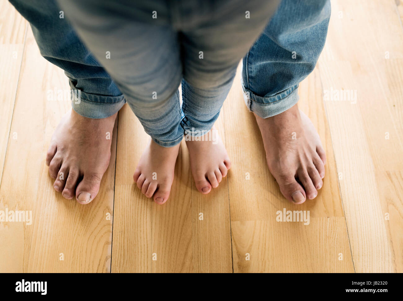 Beautiful young family. Bare feet of father and daughter. - Stock Image