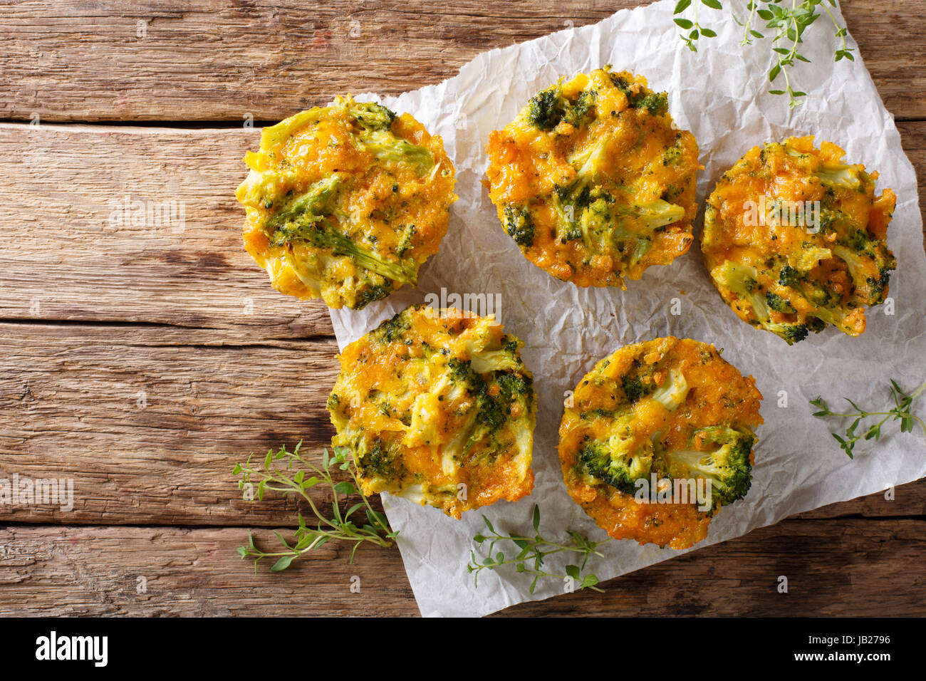 Broccoli Muffins with cheddar cheese and thyme close-up on the table. horizontal view from above - Stock Image