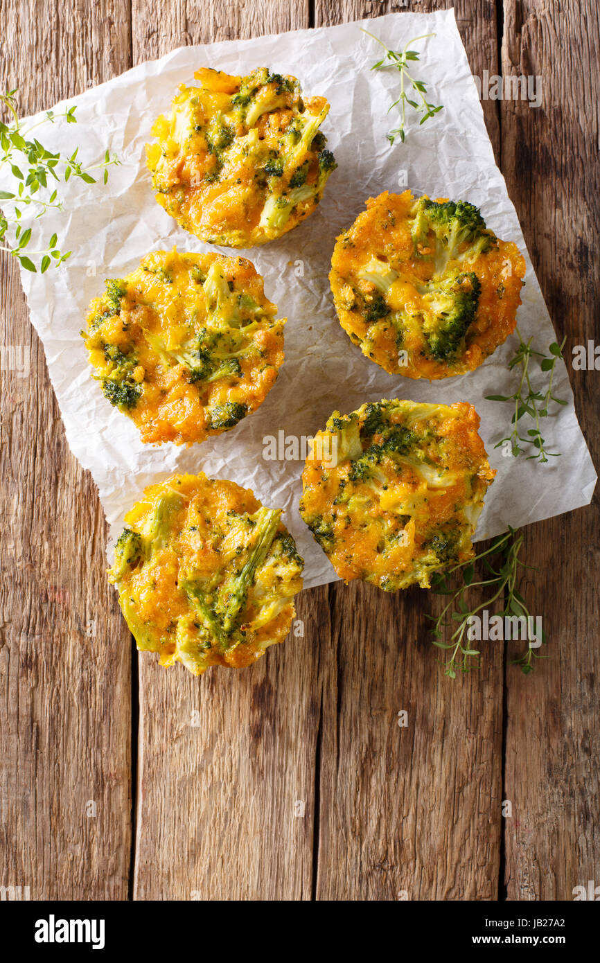 Broccoli Muffins with cheddar cheese and thyme close-up on the table. Vertical view from above - Stock Image