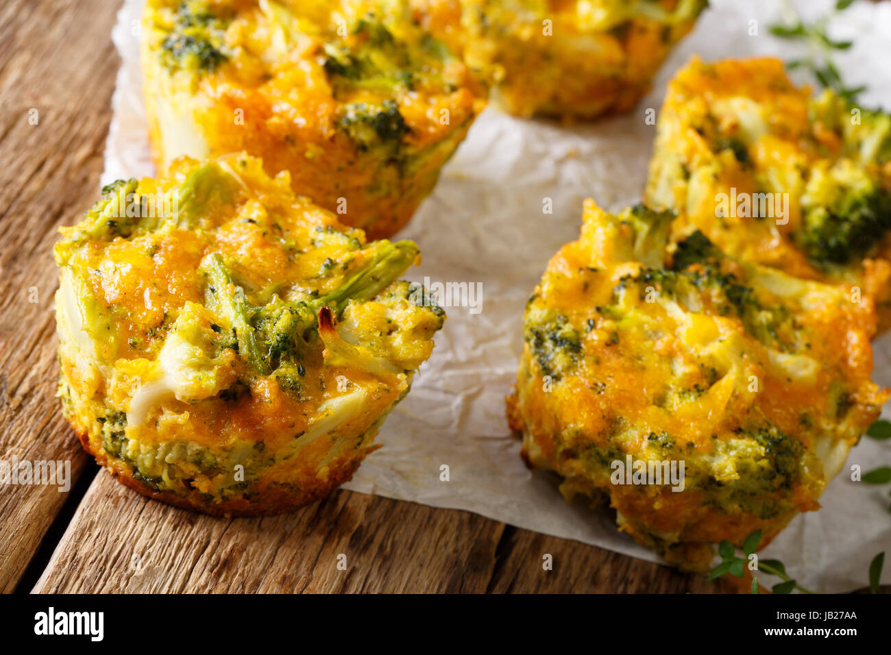 Healthy snack Broccoli muffins with cheddar cheese and thyme close-up on the table. horizontal - Stock Image