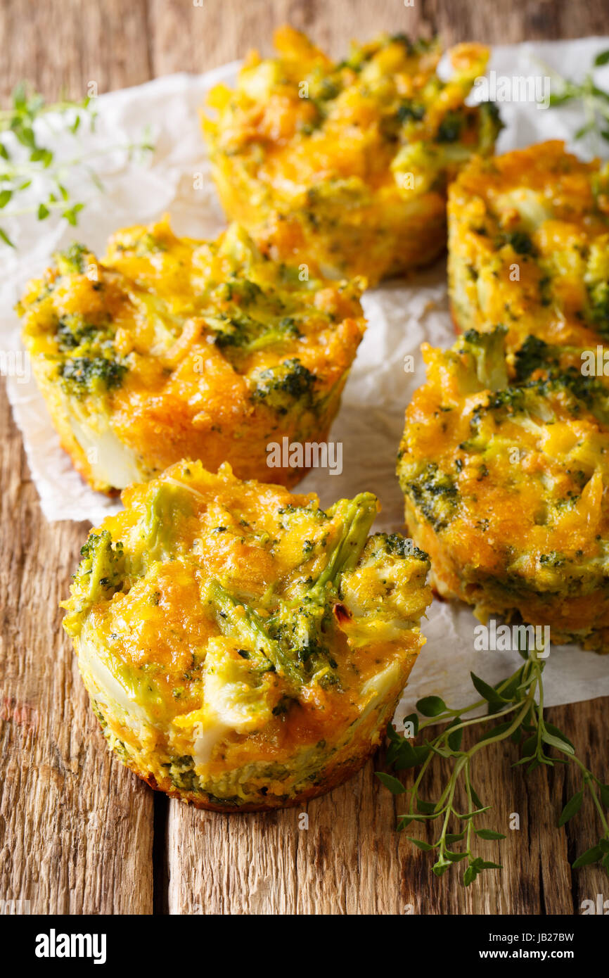 Healthy snack Broccoli muffins with cheddar cheese and thyme close-up on the table. Vertical - Stock Image