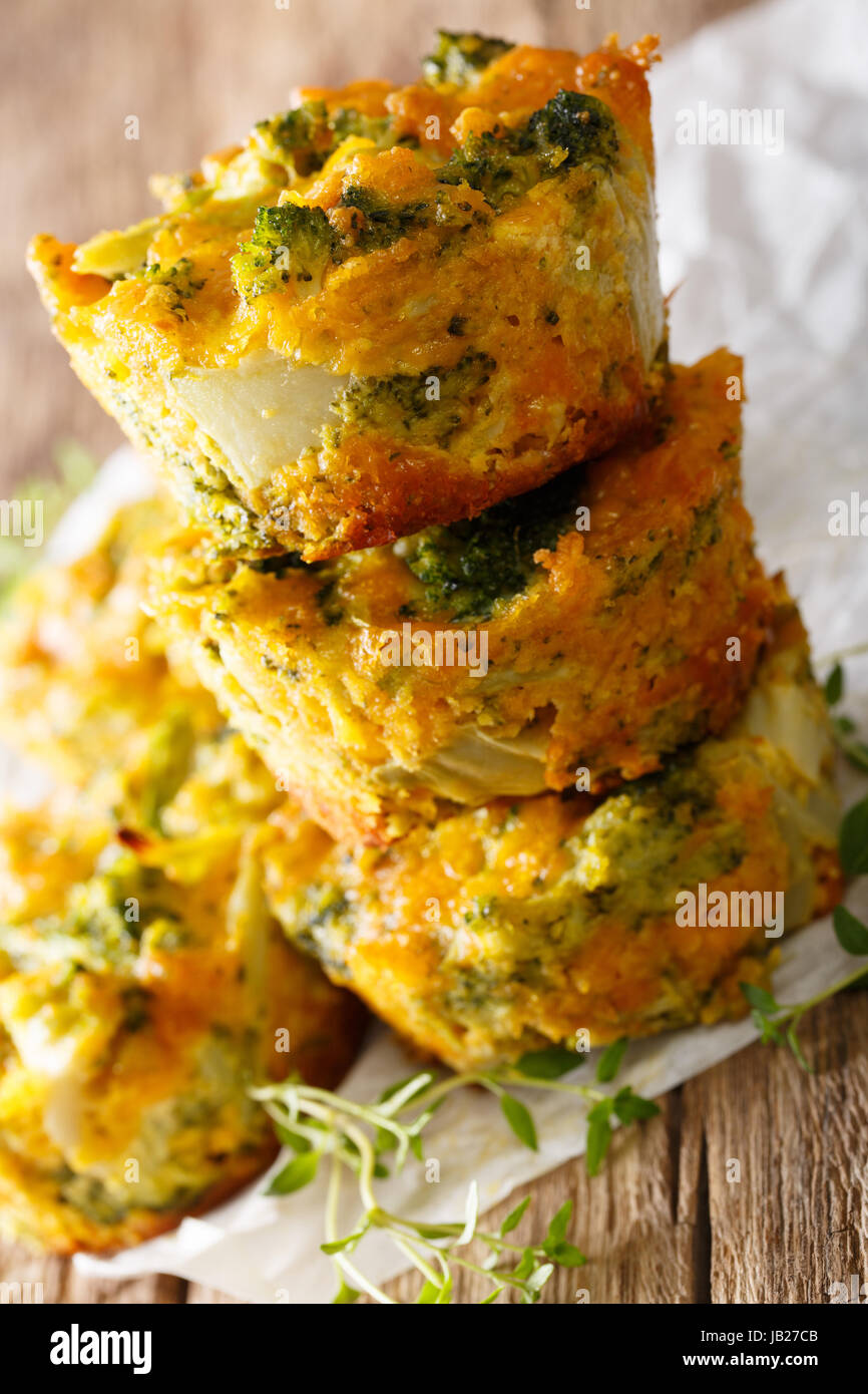 Hearty and delicious appetizer: broccoli muffins with cheese macro on the table. vertical - Stock Image