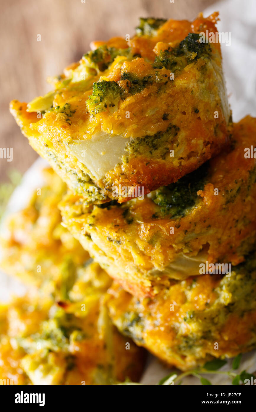 Nourishing food: broccoli muffins with cheddar cheese close-up on the table. vertical - Stock Image