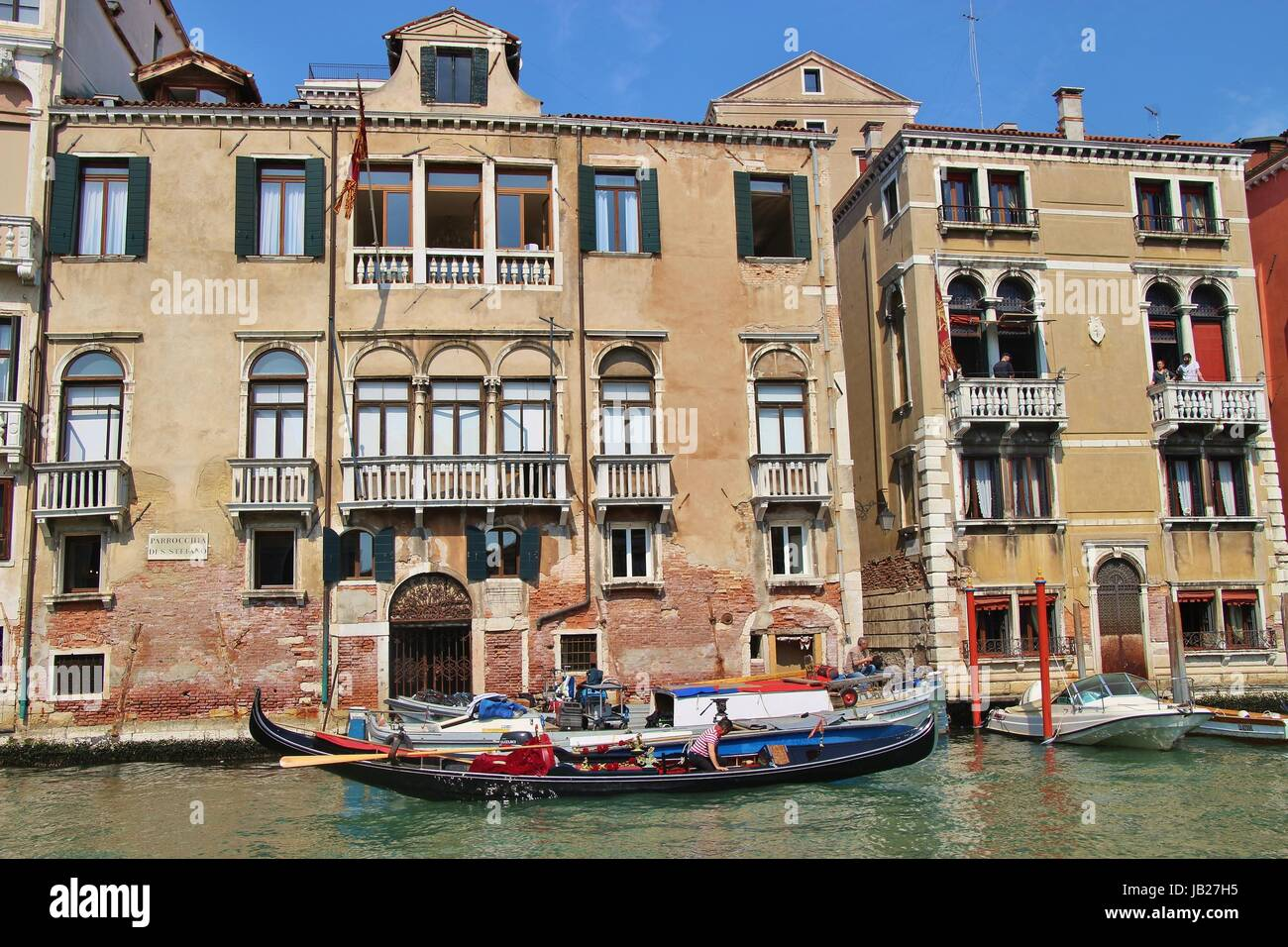 Gondola and buildings on the Grand Canal, San Stefano. Everyday scene with inhabitants on the balconies. Venice, - Stock Image