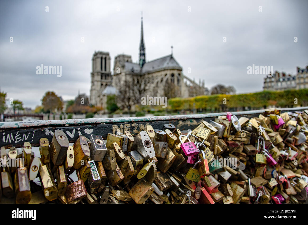 Love locks on the bridge with Notre-Dame cathedral in the background - Stock Image