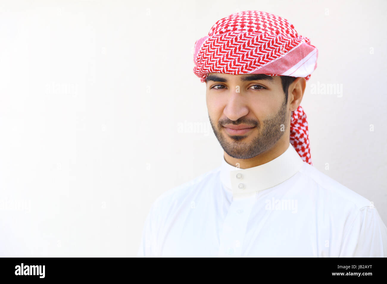 Portrait of an arab saudi man outdoor on a white wall Stock Photo