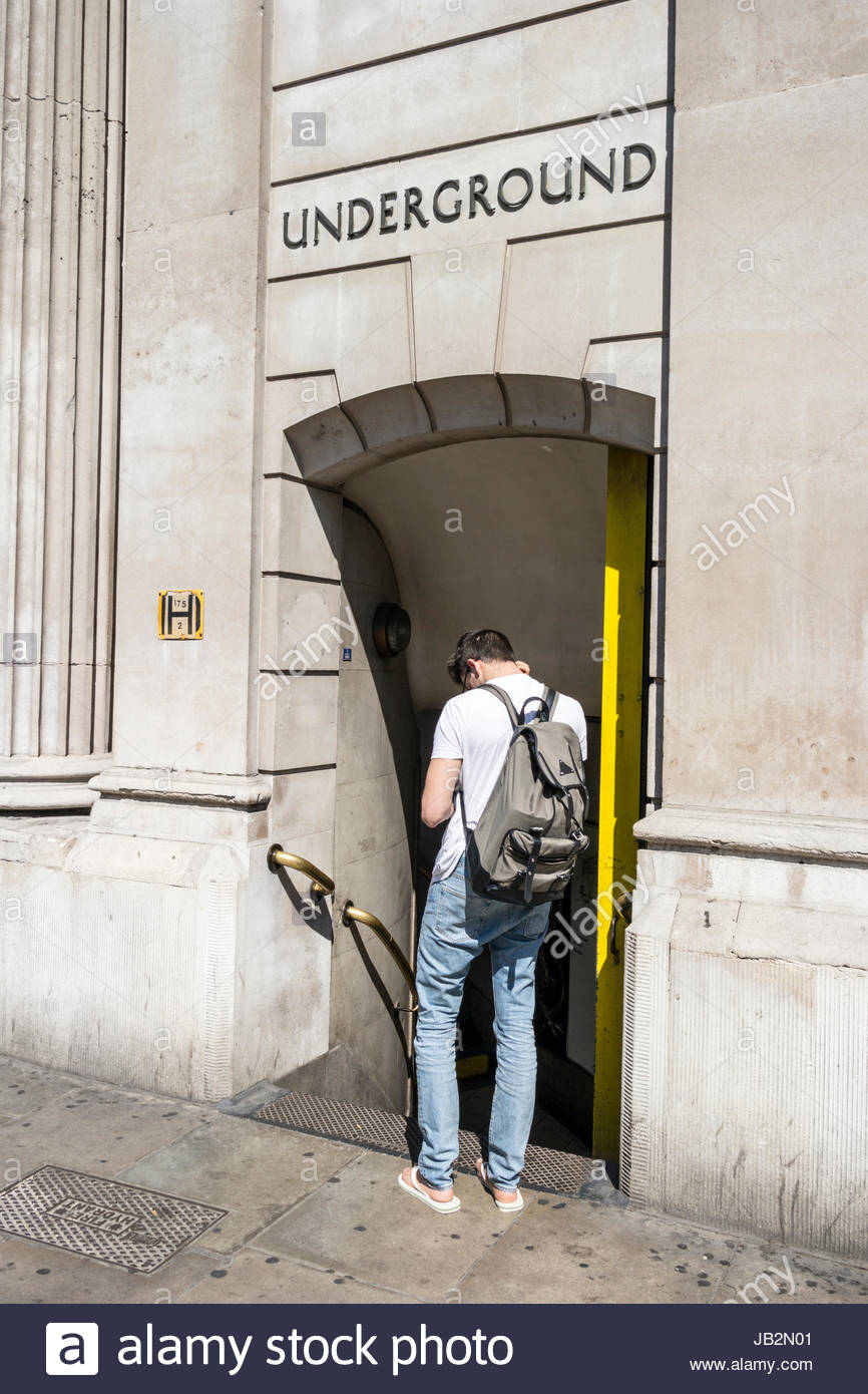 Man standing outside the entrance to Bank Underground station in central London, England, UK - Stock Image