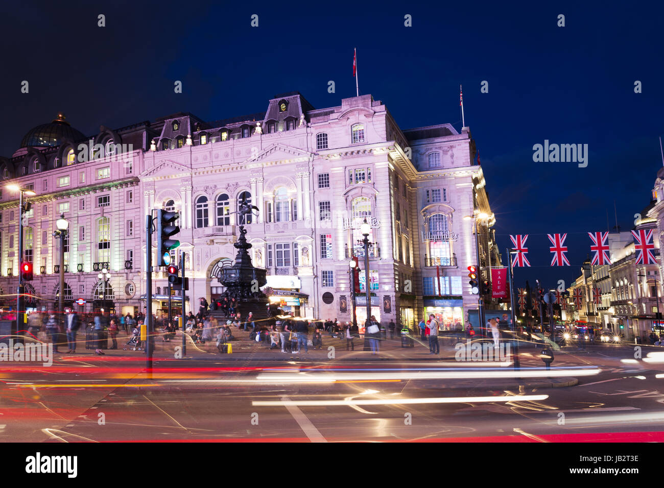 Popular tourist Picadilly circus with flags union jack in night lights illumination in London, England, United Kingdom - Stock Image