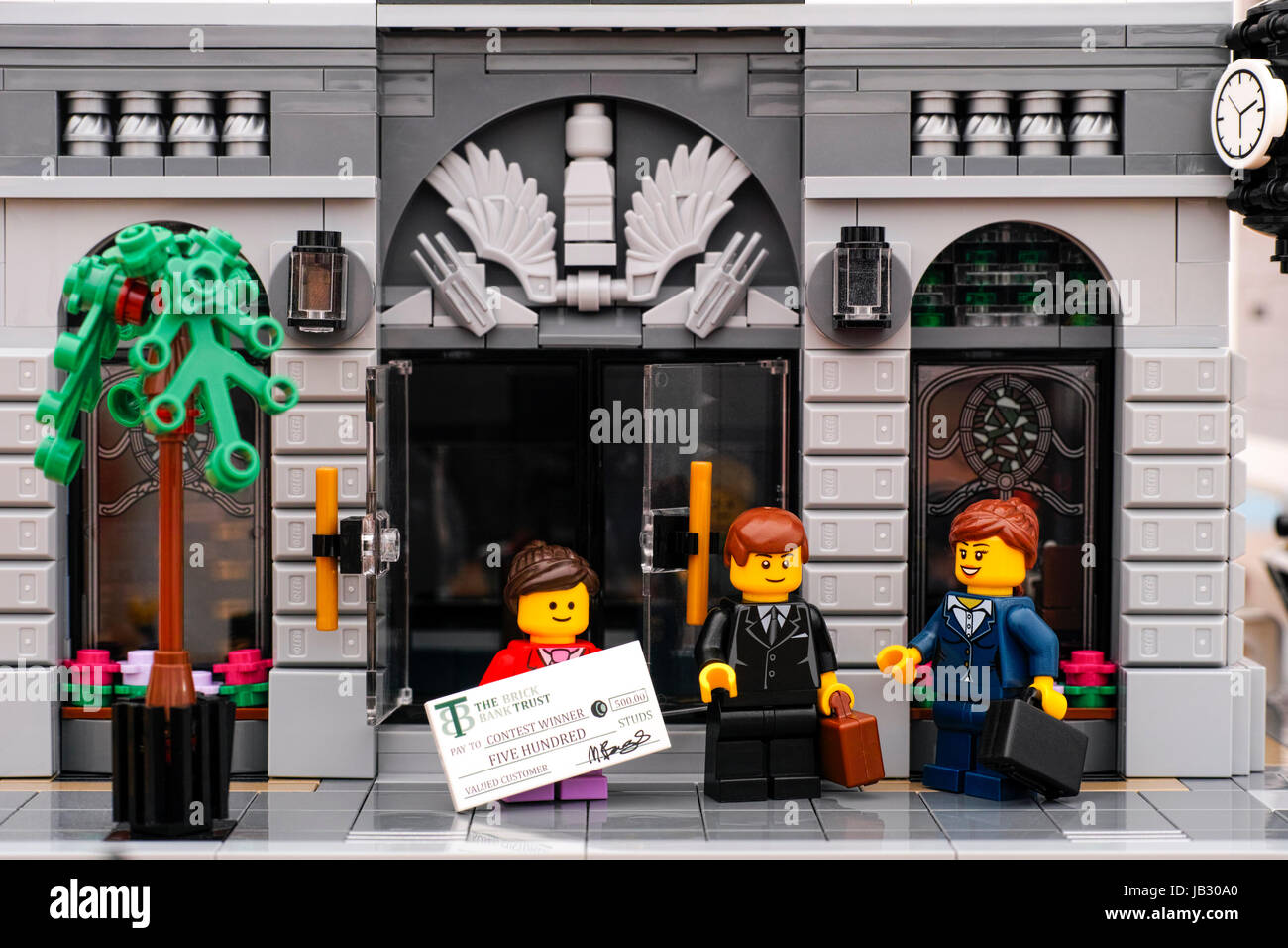 Tambov, Russian Federation - January 21, 2017 Lego bank. Lego girl with prize check comes out of the bank door. - Stock Image