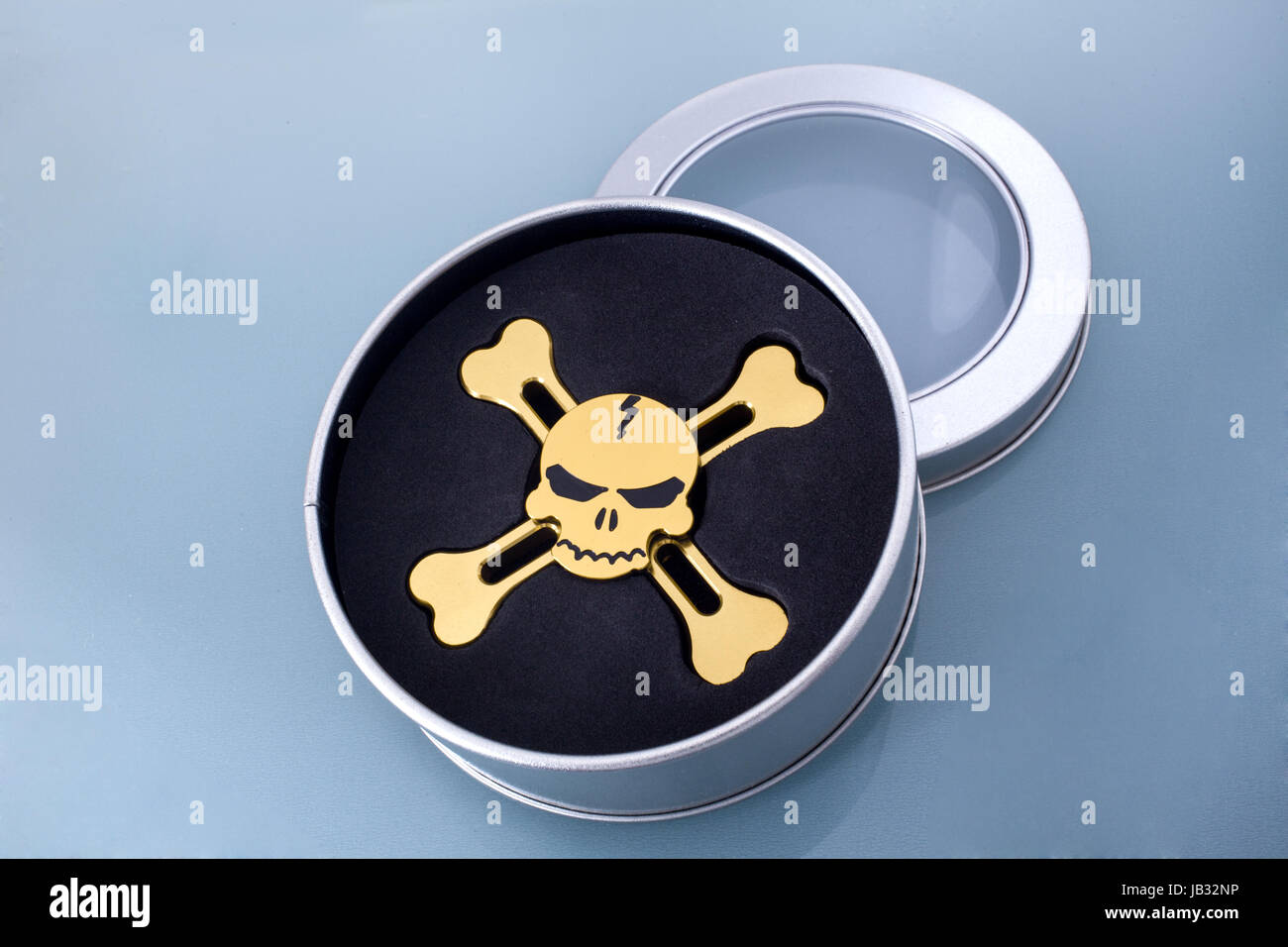 Golden spinner in the form of a skull on a blue background - Stock Image