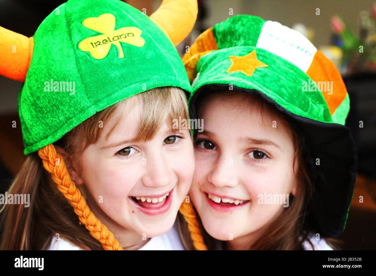 Two girls, children hugging wearing St. Patrick's Day hats in Dublin Ireland - Stock Image