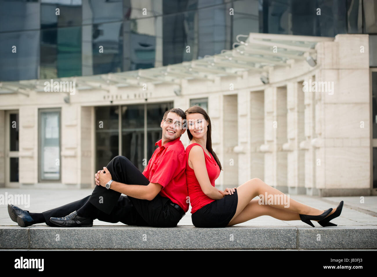 Young business couple relaxing leant with backs on street - Stock Image