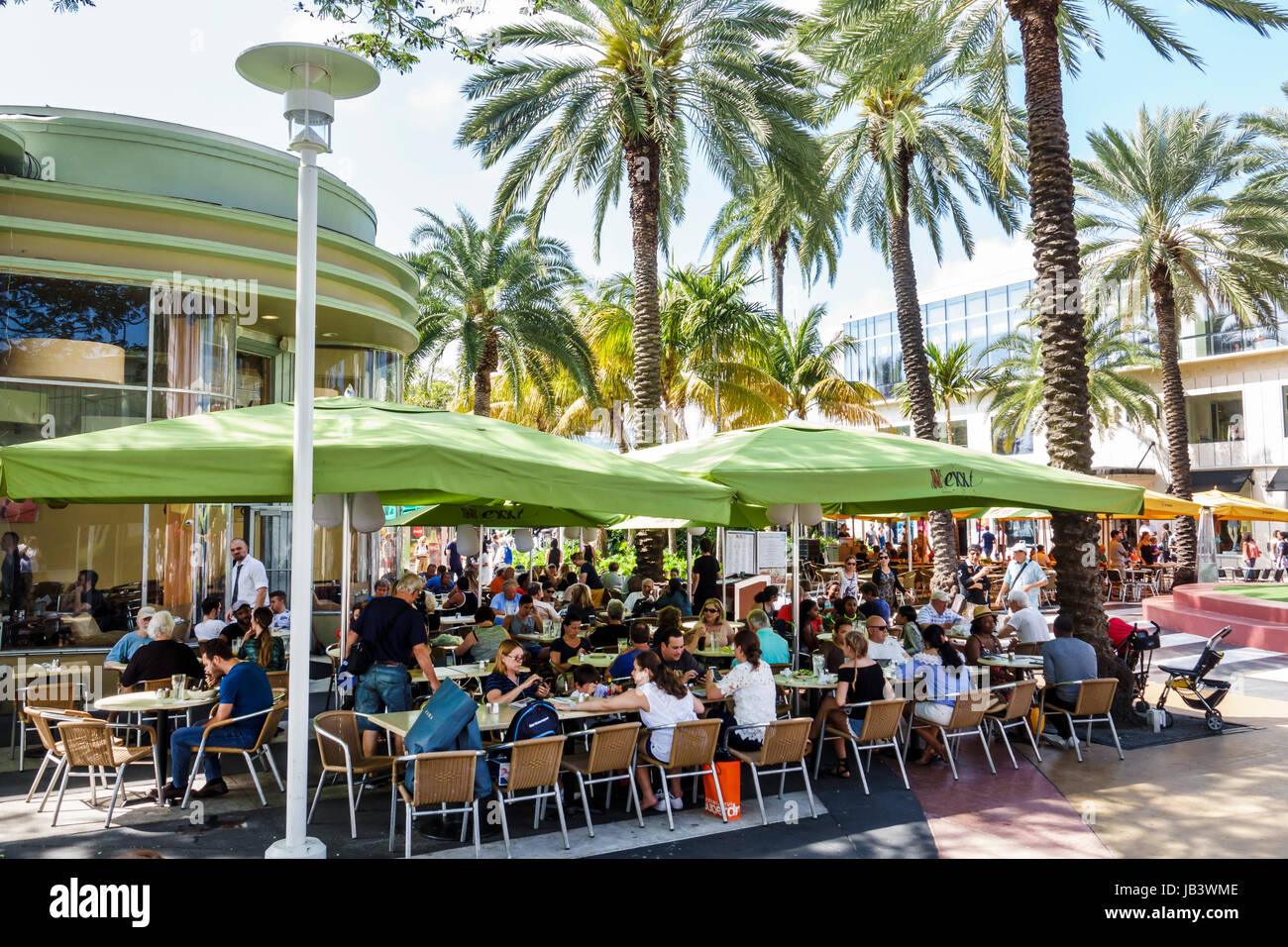 Miami Beach Florida Lincoln Road pedestrian mall Nexxt Cafe restaurant outdoor dining al fresco umbrellas crowded - Stock Image